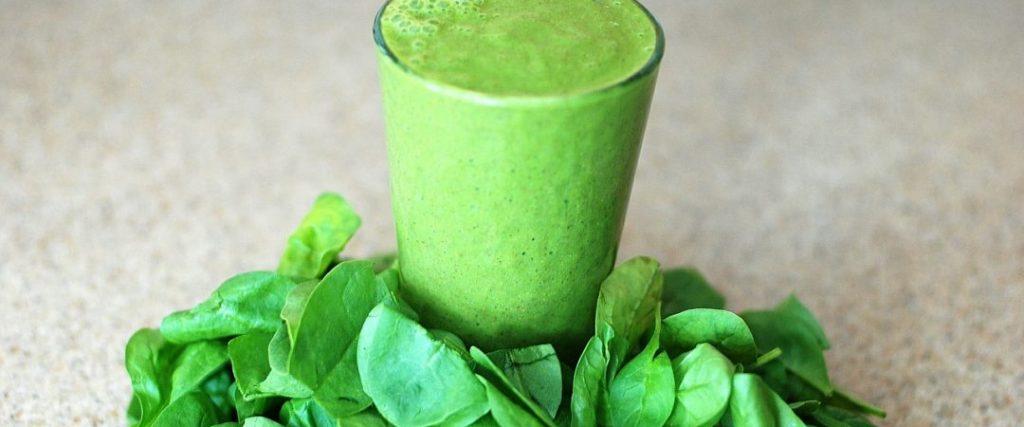 Raw spinach around a vegan protein shake