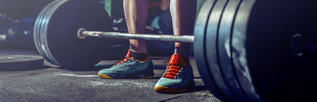 man deadlifting with weightlifting shoes