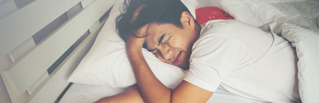 man having trouble sleeping on feather pillow