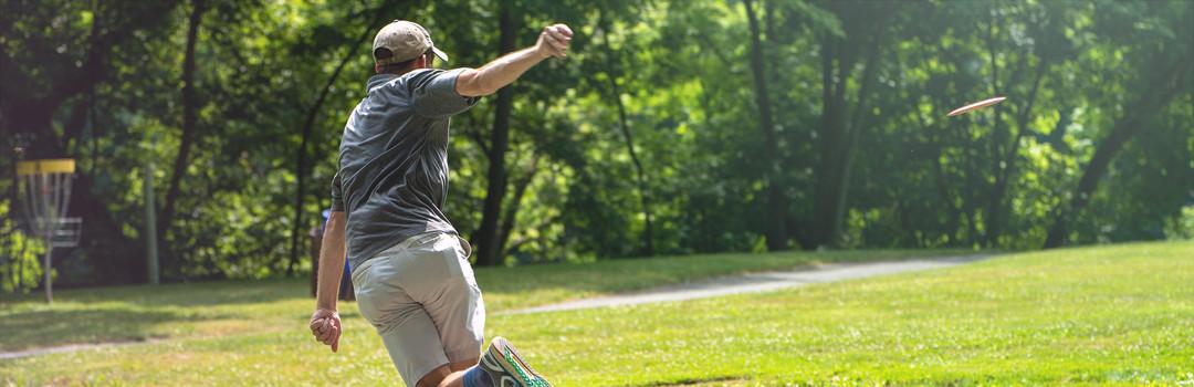 man throwing disc golf disc