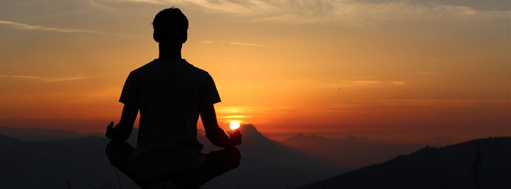 silhouette of a man meditating in front of a sunset