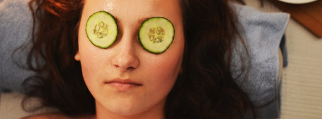 A woman with cucumbers on her eyes