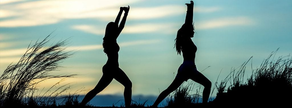 silhouette of two women in yoga poses