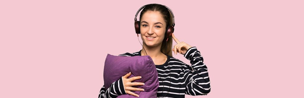woman with pillow and sleeping ear muffs
